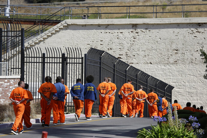 FILE - In this Aug. 16, 2016, file photo, general population inmates walk in a line at San Quentin State Prison in San Quentin, Calif. A California appeals court has ordered state corrections officials to cut the population of one of the world's most famous prisons to less than half of its designed capacity, citing officials'