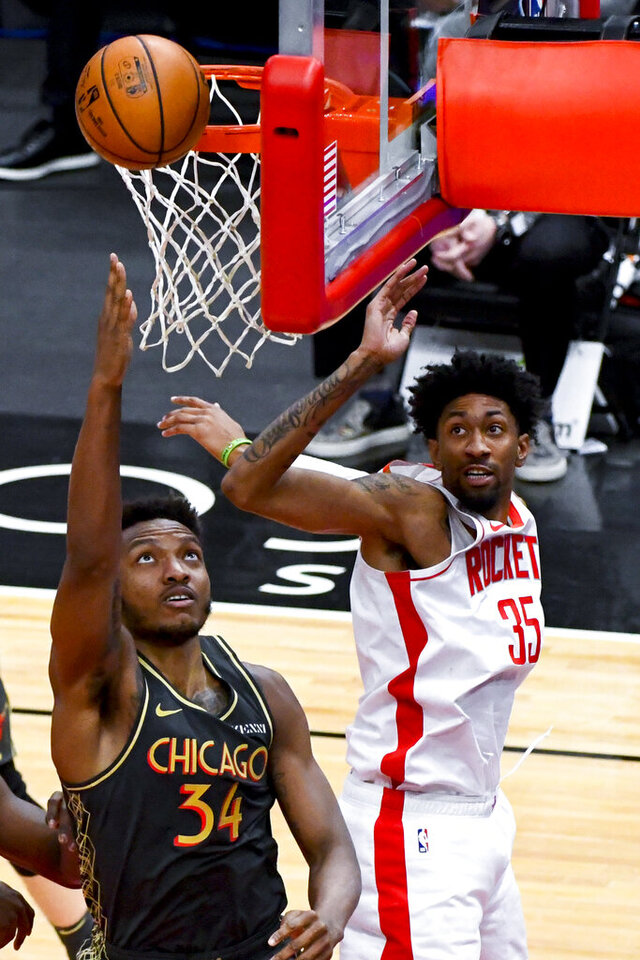 Chicago Bulls center Wendell Carter Jr. (34) shoots past Houston Rockets center Christian Wood (35) during the first half of an NBA basketball game Monday, Jan. 18, 2021, in Chicago. (AP Photo/Matt Marton)