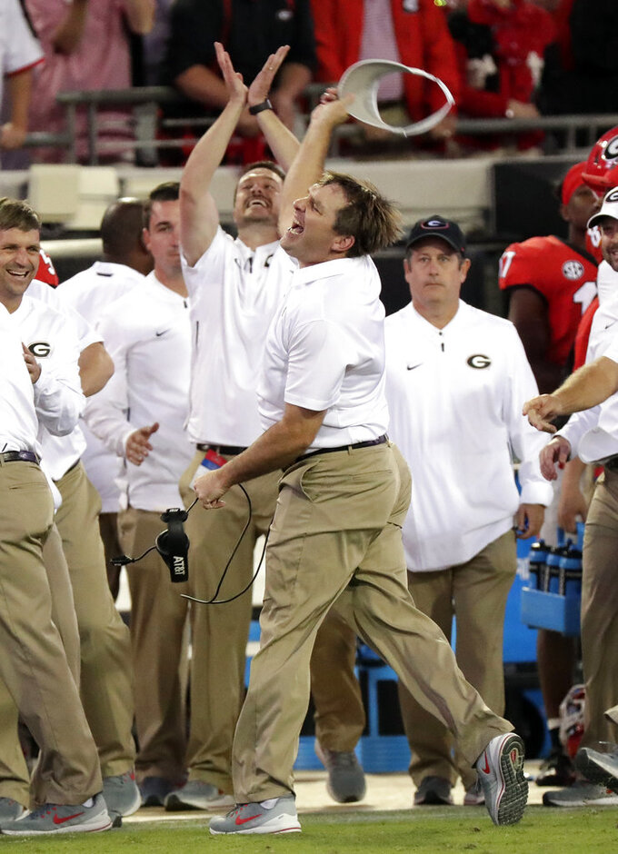 Georgia head coach Kirby Smart, center, celebrates as he runs down the sideline during the final seconds defeating Florida 36-17 in an NCAA college football game Saturday, Oct. 27, 2018, in Jacksonville, Fla. (AP Photo/John Raoux)