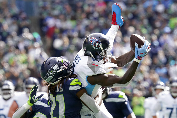 Tennessee Titans wide receiver Julio Jones, right, is tackled by Seattle Seahawks cornerback Tre Flowers, left, as he comes down with a reception during the first half of an NFL football game, Sunday, Sept. 19, 2021, in Seattle. (AP Photo/Elaine Thompson)