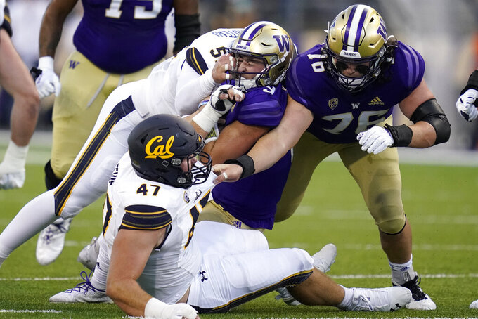 Washington quarterback Dylan Morris, center, is tackled by California linebacker Braxten Croteau, upper left, during the first half of an NCAA college football game, Saturday, Sept. 25, 2021, in Seattle. (AP Photo/Elaine Thompson)