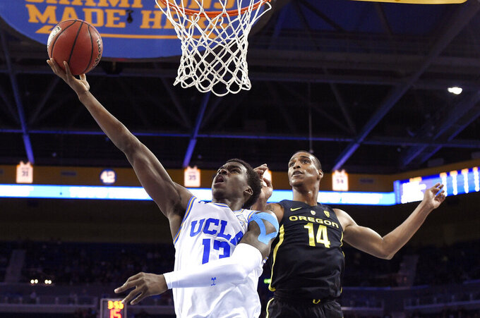 UCLA guard Kris Wilkes, left, shoots as Oregon forward Kenny Wooten defends during the first half of an NCAA college basketball game Saturday, Feb. 23, 2019, in Los Angeles. (AP Photo/Mark J. Terrill)