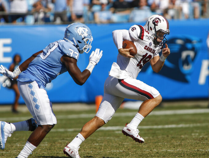South Carolina quarterback Jake Bentley, right, carries the football as North Carolina linebacker Allen Cater chases in the first half of an NCAA college football game in Charlotte, N.C., Saturday, Aug. 31, 2019. (AP Photo/Nell Redmond)