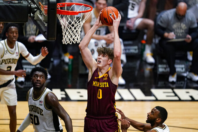 Minnesota center Liam Robbins (0) goes up for a dunk over Purdue forward Trevion Williams (50) during the first half of an NCAA college basketball game in West Lafayette, Ind., Saturday, Jan. 30, 2021. (AP Photo/Michael Conroy)