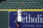 Houston Astros right fielder Josh Reddick reaches for a home run by Arizona Diamondbacks' Kole Calhoun during the eighth inning of a baseball game Friday, Sept. 18, 2020, in Houston. (AP Photo/David J. Phillip)