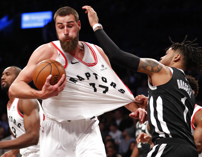 Brooklyn Nets guard D'Angelo Russell, right, grabs the jersey of Toronto Raptors center Jonas Valanciunas (17), for which he drew a foul call, Tuesday, March 13, 2018, in New York. The Raptors defeated the Nets 116-102. (AP Photo/Kathy Willens)