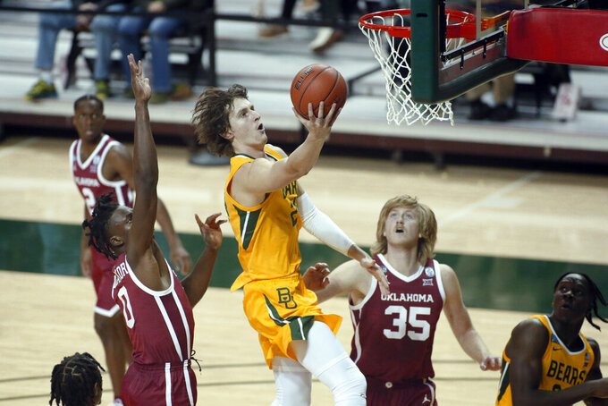 Baylor guard Matthew Mayer, center, goes to the basket on Oklahoma forward Victor Iwuakor, left and Oklahoma forward Brady Manek, right, during the second half of an NCAA college basketball game on Wednesday, Jan. 6, 2021, in Waco, Texas. (AP Photo/Ray Carlin)