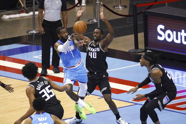 Houston Rockets guard John Wall passes the ball around Sacramento Kings' Harrison Barnes during the first half of an NBA basketball game Thursday, Dec. 31, 2020, in Houston. (AP Photo/Richard Carson)
