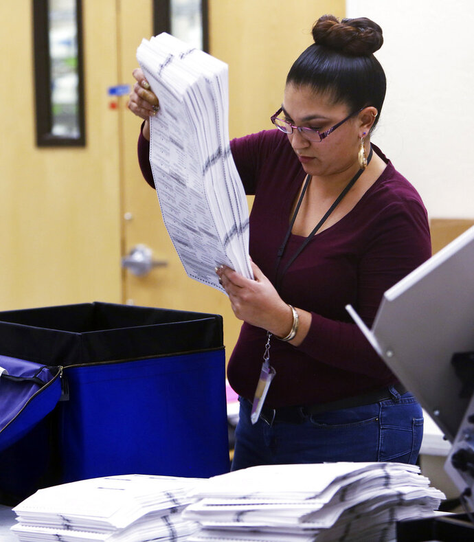 An elections worker prepares ballots before inserting them into a counting machine at Pima County Elections in Tucson, Ariz., Monday, Nov. 12, 2018.  (Rick Wiley /Arizona Daily Star via AP)