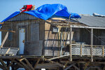 A man attaches a tarp to a damaged building Thursday, Oct. 29, 2020, as Cocodrie, La., residents try to repair their homes hit by Hurricane Zeta. Residents slowly returned to their homes and fishing camps to assess the damage left by the storm. (Chris Granger/The Advocate via AP)