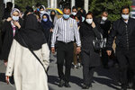 People wearing protective face masks to help prevent the spread of the coronavirus walk in downtown Tehran, Iran, Monday, April 5, 2021. Iran shattered its daily record for new coronavirus infections Wednesday for the second consecutive day, with recorded cases soaring to 20,954. (AP Photo/Vahid Salemi)