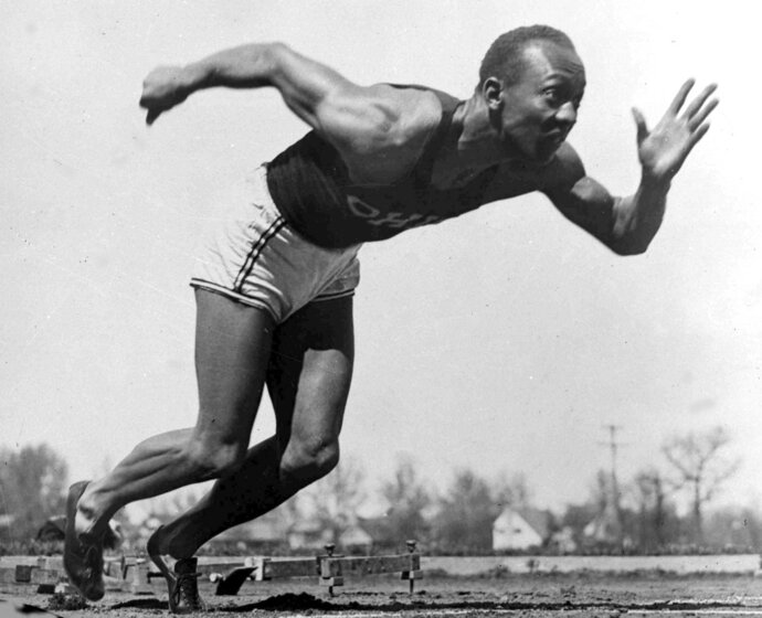 FILE - In this Aug. 5, 1936 file photo, American athlete Jesse Owens practices in the Olympic Village in Berlin. Two of Owens' daughters are expected to accompany Ohio Gov. John Kasich during dedication events at Jesse Owens Memorial Stadium in Columbus, Ohio, Tuesday, July 17, 2018, and later in the day at Miner's Memorial Park in McConnelsville, Ohio.  (AP Photo, File)