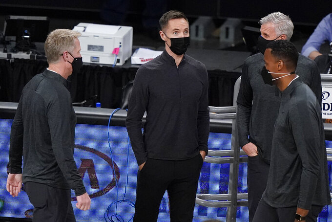 Brooklyn Nets coach Steve Nash, center, talks with Golden State Warriors coach Steve Kerr, left, and other coaches before an NBA basketball game, Nash's debut in the regular season, Tuesday, Dec. 22, 2020, in New York. (AP Photo/Kathy Willens)