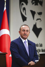 Turkey's Foreign Minister Mevlut Cavusoglu speaks during news conference in Ankara, Turkey, Tuesday, Aug. 11, 2020. Tension remains high between Greece and Turkey, whose warships are in the eastern Mediterranean where Turkey has sent a research vessel to carry out seismic research for energy resources in an area Greece says is on its continental shelf. Cavusoglu said Turkey was determined press ahead with its efforts to search for resources in the Eastern Mediterranean. (Cam Ozdel/Turkish Foreign Ministry via AP, Pool)