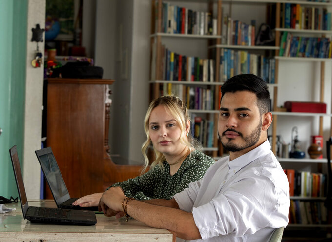 Leonardo de Carvalho Leal, right, and Mayara Stelle, who administer the Twitter account Sleeping Giants Brazil, use their computers in Sao Paulo, Brazil, Friday, Dec. 11, 2020. Sleeping Giants is a platform for activism whose stated mission is to attack the financing of hate speech and dissemination of fake news. (AP Photo/Andre Penner)