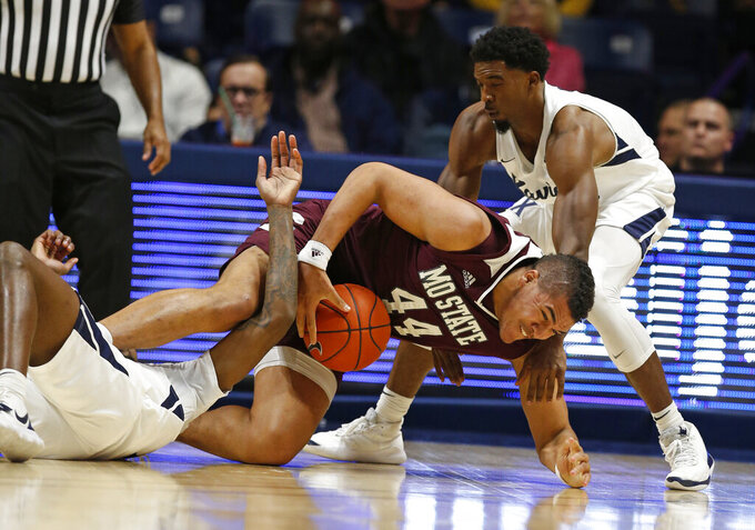 Missouri State forward Gaige Prim (44) falls as he becomes entangled with Xavier forward Naji Marshall, left, and guard Quentin Goodin, right, during the first half of an NCAA college basketball game, Friday Nov. 15, 2019, in Cincinnati. (AP Photo/Gary Landers)