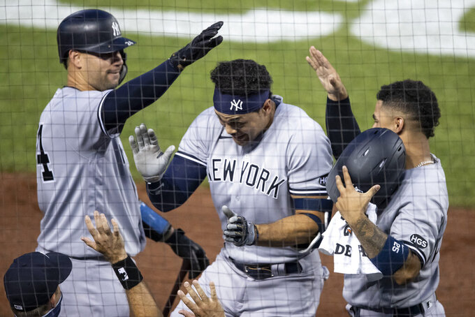 New York Yankees' Gary Sanchez, left, and Gleyber Torres, right, celebrate with Giancarlo Stanton, center, after Stanton's solo home run during the fourth inning of a baseball game against the Washington Nationals at Nationals Park, Saturday, July 25, 2020, in Washington. (AP Photo/Alex Brandon)