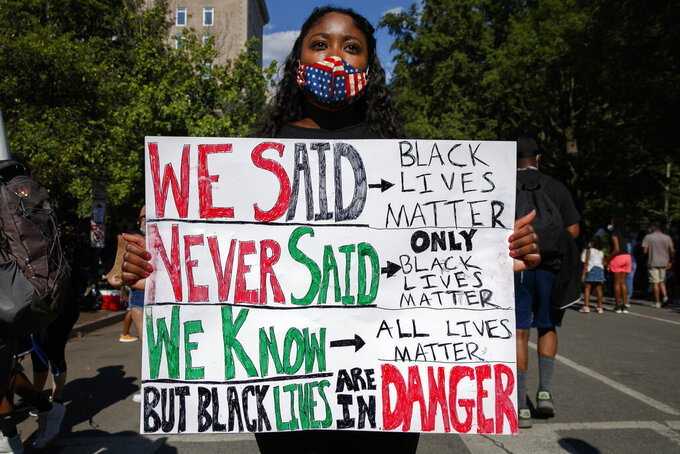 Esther Newman, of Washington, holds a sign as she joins protesters Sunday, June 7, 2020, near the White House in Washington over the death of George Floyd, who died May 25 after being restrained by police in Minneapolis(AP Photo/Jacquelyn Martin)