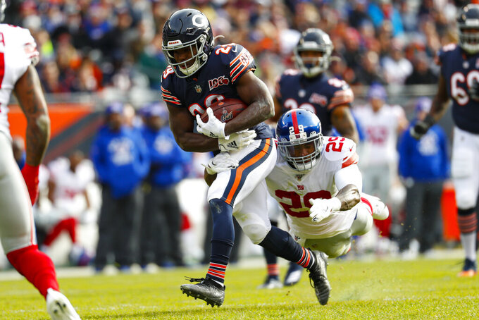 Chicago Bears running back Tarik Cohen, center left, is tackled by New York Giants outside linebacker Deone Bucannon, center right, during the first half of an NFL football game in Chicago, Sunday, Nov. 24, 2019. (AP Photo/Paul Sancya)