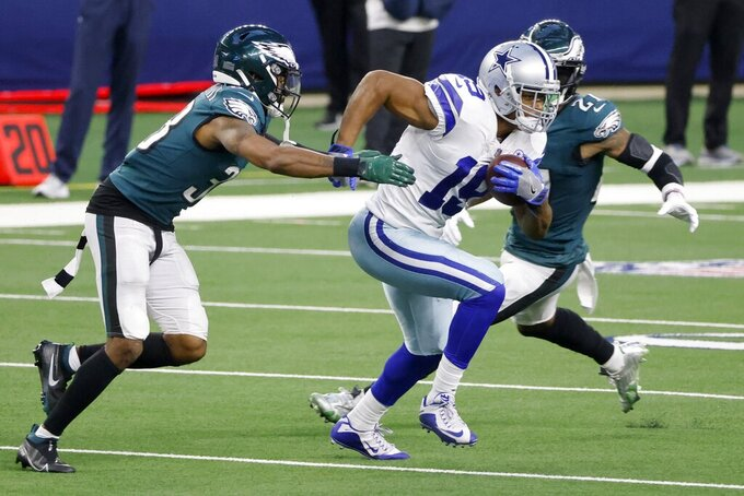 Philadelphia Eagles cornerback Michael Jacquet (38) reaches out to stop Dallas Cowboys wide receiver Amari Cooper (19) who gains long yardage after catching a pass in the second half of an NFL football game in Arlington, Texas, Sunday, Dec. 27. 2020. (AP Photo/Michael Ainsworth)