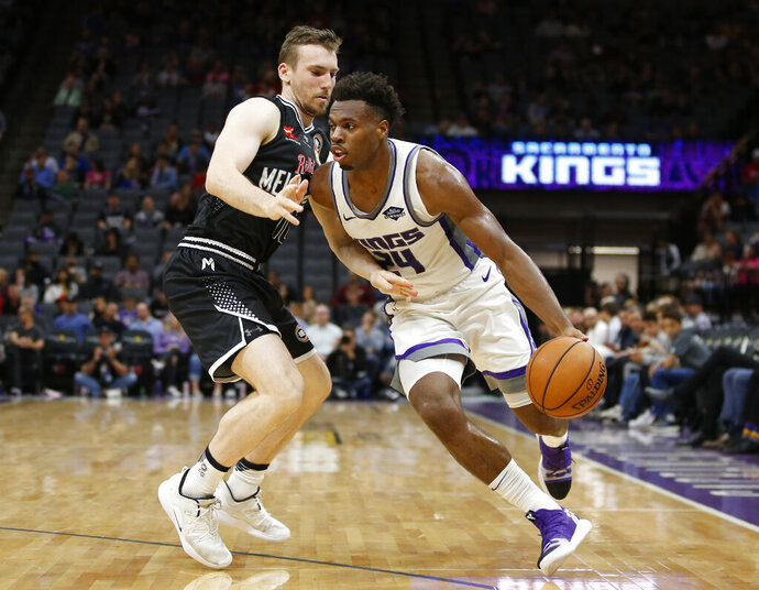 Sacramento Kings guard Buddy Hield, right, drives against Melbourne United guard Chris Goulding during the second half of an NBA exhibition basketball game in Sacramento, Calif., Wednesday, Oct. 16, 2019. The Kings won 124-110. (AP Photo/Rich Pedroncelli)