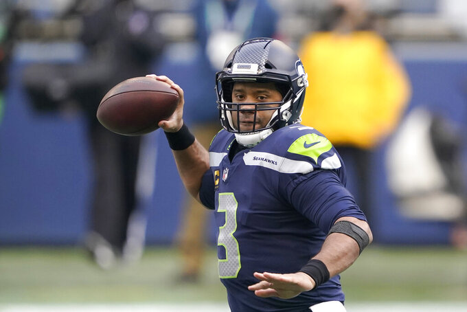 Seattle Seahawks quarterback Russell Wilson readies a pass against the Los Angeles Rams during the first half of an NFL wild-card playoff football game, Saturday, Jan. 9, 2021, in Seattle. (AP Photo/Ted S. Warren)