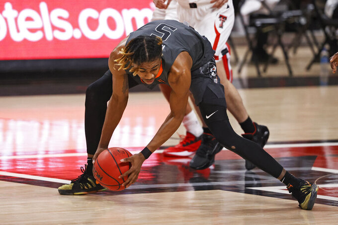 Oklahoma State's Rondel Walker (5) dives for the loose ball during the first half of an NCAA college basketball game against Texas Tech, Saturday, Jan. 2, 2021, in Lubbock, Texas. (AP Photo/Brad Tollefson)