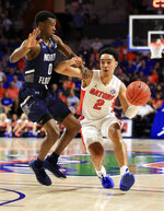 Florida guard Andrew Nembhard (2) drives to the basket past North Florida guard Emmanuel Adedoyin (0) during the first half of an NCAA college basketball game Tuesday, Nov. 5, 2019, in Gainesville, Fla. (AP Photo/Matt Stamey)