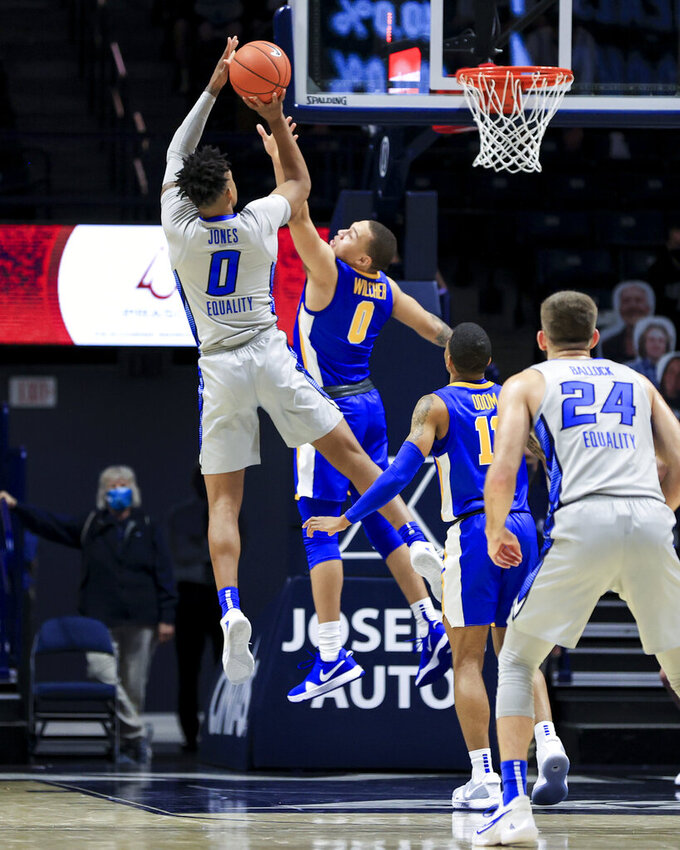 Creighton guard Antwann Jones, left, attempts to shoot against Xavier guard C.J. Wilcher (0) in the first half of an NCAA college basketball game, Saturday, Feb. 27, 2021, in Cincinnati. (AP Photo/Aaron Doster)