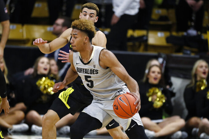 Colorado guard D'Shawn Schwartz, front, drives to the rim past Oregon guard Chris Duarte in the first half of an NCAA college basketball game Thursday, Jan. 2, 2020, in Boulder, Colo. (AP Photo/David Zalubowski)