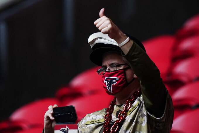 Fans watch teams warm up the first half of an NFL football game between the Atlanta Falcons and the Denver Broncos, Sunday, Nov. 8, 2020, in Atlanta. (AP Photo/Brynn Anderson)