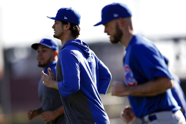 Chicago Cubs pitcher Yu Darvish, center, runs with other pitchers during a spring training baseball workout Wednesday, Feb. 12, 2020, in Mesa, Ariz. (AP Photo/Gregory Bull)