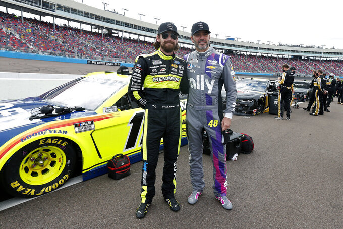 Jimmie Johnson, right, stops to have a photo taken with fellow driver Ryan Blaney prior to a NASCAR Cup Series auto race at Phoenix Raceway, Sunday, Nov. 8, 2020, in Avondale, Ariz. (AP Photo/Ralph Freso)