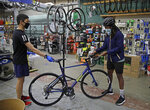 In this Friday, May 15, 2020 photo, Joel Johnson, right, takes delivery of his new bicycle at the Sports Basement store in San Francisco. Johnson hadn't owned a bicycle since he was 15, but soon after the coronavirus pandemic led to a shelter in place order in San Francisco, he bought a bike to avoid crowded public trains and buses. He is among thousands of cooped-up Americans snapping up new bicycles or dusting off decades-old bikes to stay fit, keep their mental sanity or have a safe alternative to public transportation. (AP Photo/Ben Margot)