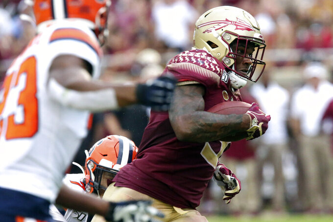 Florida State's Cam Akers, right, picks up yardage during the fourth quarter of an NCAA college football game against Syracuse, Saturday, Oct. 26, 2019, in Tallahassee Fla. (AP Photo/Steve Cannon)