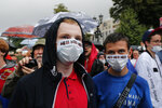 People gather to collect signatures to cancel the results of voting on amendments to the Constitution in Moscow, Russia, Wednesday, July 15, 2020. Writing on the face masks reads
