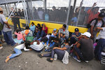 Migrants gather next to the border fence after camping out on the Gateway International Bridge that connects downtown Matamoros, Mexico with Brownsville, Thursday, Oct. 10, 2019. Migrants wanting to request asylum camped out on the international bridge leading from Mexico into Brownsville, Texas, causing a closure of the span. (AP Photo/Fernando Llano)