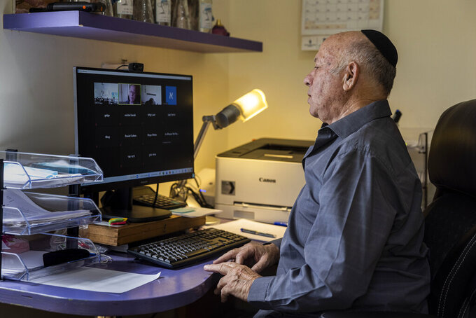 Dr Shmuel Rosenman, chairman of March of the Living gives an online lecture at his house in Moshav Hemed, Israel, Wednesday, April 7, 2021. The March of the Living is saluting medical heroes this year. The annual Holocaust education event is usually marked with a march on the grounds of the former Auschwitz death camp in Poland. But for a second straight year it is being held virtually due to the coronavirus pandemic. (AP Photo/Tsafrir Abayov)