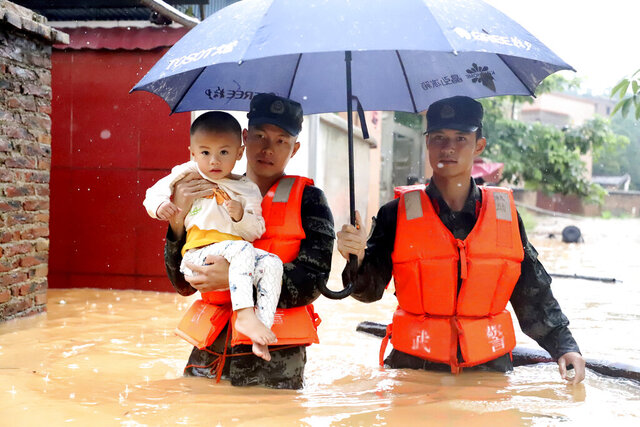 Rescuers carry a child to a boat during an evacuation of a flooded village in Qingyuan in southern China's Guangdong province on Monday, June 8, 2020. Flooding in south and central China has lead to more than a dozen deaths and forced hundreds of thousands of people from their homes, the government said Wednesday.  (Chinatopix Via AP)