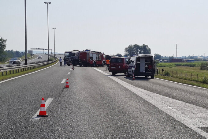 Emergency crews work at the site of a bus accident near Slavonski Brod, Croatia, Sunday, July 25, 2021. A bus swerved off a highway and crashed in Croatia early Sunday, killing 10 people and injuring at least 30 others, police said. (AP Photo/Luka Safundzic, SBonline)