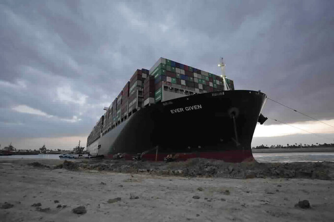 In this photo released by the Suez Canal Authority, tug boats and diggers work to free the Panama-flagged, Japanese-owned Ever Given, which is lodged across the Suez Canal, Sunday, March 28, 2021. Two additional tugboats are speeding to canal to aid efforts to free the skyscraper-sized container ship wedged for days across the crucial waterway. That's even as major shippers increasingly divert their boats out of fear the vessel may take even longer to free. (Suez Canal Authority via AP)