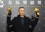 Taiwanese director Chen Yu-hsun holds his awards for Best Director and Best Original Screenplay at the 57th Golden Horse Awards in Taipei, Taiwan, Saturday, Nov. 21, 2020. Chen won for the film