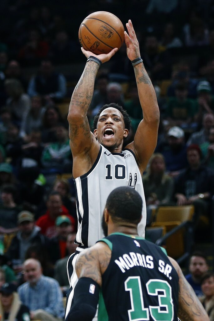 San Antonio Spurs' DeMar DeRozan (10) shoots a 3-pointer over Boston Celtics' Marcus Morris (13) during the second half of an NBA basketball game in Boston, Sunday, March 24, 2019. (AP Photo/Michael Dwyer)