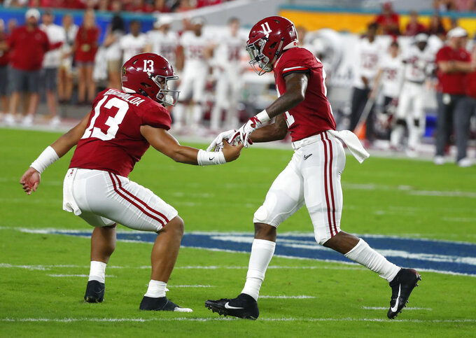 Alabama quarterback Tua Tagovailoa (13) congratulates wide receiver Henry Ruggs III (11) after Ruggs scored a touchdown, during the first half of the Orange Bowl NCAA college football game against Oklahoma, Saturday, Dec. 29, 2018, in Miami Gardens, Fla. (AP Photo/Wilfredo Lee)