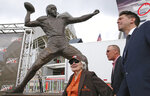 Beverly Graham, left, wife of Cleveland Browns quarterback great Otto Graham, checks out the bronze statue of her husband with Browns general manager John Dorsey, center, and Graham's grandson Ryan Vanname after the unveiling ceremony, Saturday, Sept. 7, 2019, at FirstEnergy Stadium in Cleveland, Ohio.  Graham's remarkable decade of dominance with the Browns has been immortalized. The team unveiled a bronze statue on Saturday, Sept. 7, 2019, outside FirstEnergy Stadium of the late Hall of Fame quarterback, who led Cleveland to 10 championship games in 10 seasons. (John Kuntz/cleveland.com via AP)
