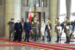 In this photo released by the official website of the office of the Iranian Presidency, Iraqi Prime Minister Mustafa al-Kadhimi, fourth left, reviews an honor guard as he is welcomed by President Hassan Rouhani, second left, as they all wear protective face masks to help prevent spread of the coronavirus, during an official arrival ceremony, in Tehran, Iran, Tuesday, July 21, 2020. (Iranian Presidency Office via AP)