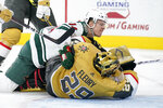 Minnesota Wild center Joel Eriksson Ek (14) falls onto Vegas Golden Knights goaltender Marc-Andre Fleury (29) after scoring during the third period of an NHL hockey game Saturday, April 3, 2021, in Las Vegas. (AP Photo/John Locher)