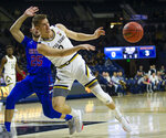 Notre Dame's Rex Pflueger (0) dishes out a pass defended by Presbyterian's JC Younger (25) during an NCAA college basketball game Monday, Nov. 18, 2019, in South Bend, Ind. (Michael Caterina/South Bend Tribune via AP)