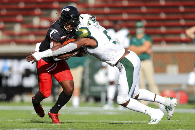 Cincinnati wide receiver Michael Young, left, makes a catch as he is tackled by South Florida linebacker Antonio Grier, right, during the first half of an NCAA college football game, Saturday, Oct. 3, 2020, in Cincinnati. (AP Photo/Aaron Doster)