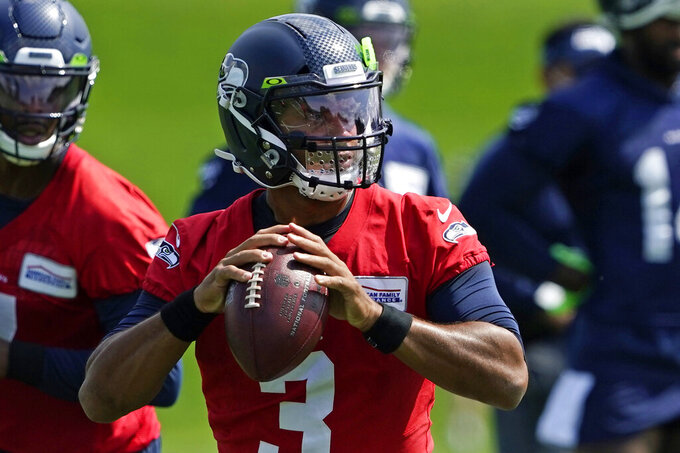 Seattle Seahawks quarterback Russell Wilson looks to pass during a practice drill at NFL football training camp, Wednesday, Aug. 12, 2020, in Renton, Wash. (AP Photo/Ted S. Warren, Pool)